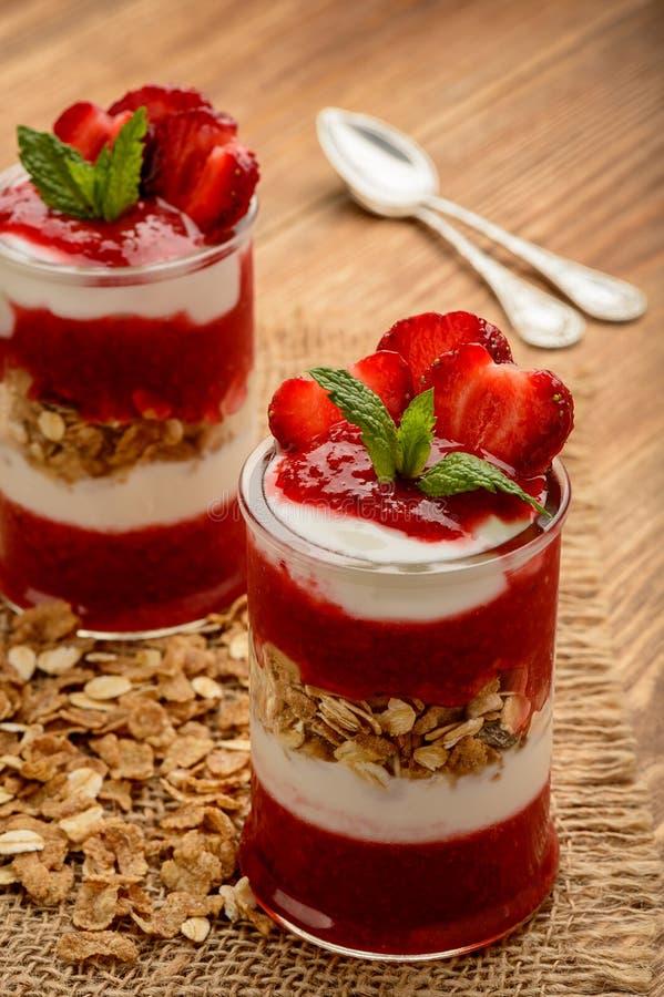 Sund yougurtefterrätt med jordgubbemousse, mysli och jordgubbar royaltyfria bilder