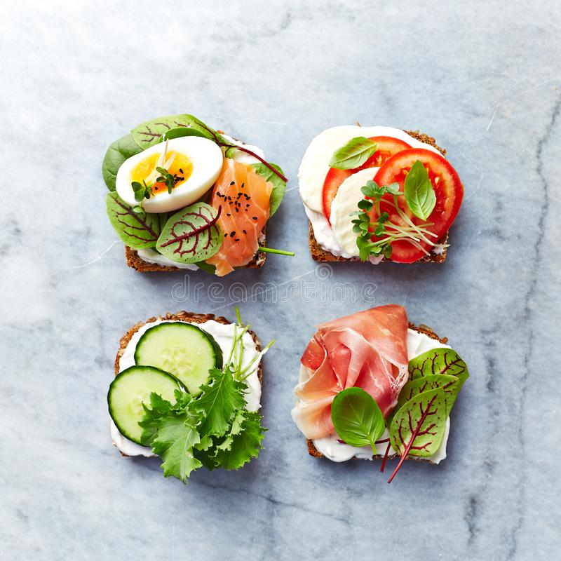 Sunda öppna smörgåsar med grönsaker, laxen, skinka, örter och mjuk ost arkivfoton