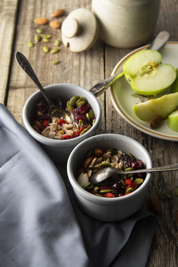 Sunda breakfastTwobunkar av mysli med havre, muttrar och torkade frukter - äpplen, kådor, pumpafrö och mandlar på trätabelle royaltyfri foto