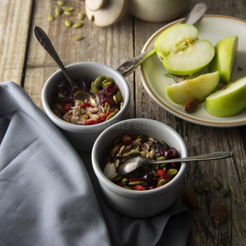 Sunda breakfastTwobunkar av mysli med havre, muttrar och torkade frukter - äpplen, kådor, pumpafrö och mandlar på trätabelle royaltyfria bilder