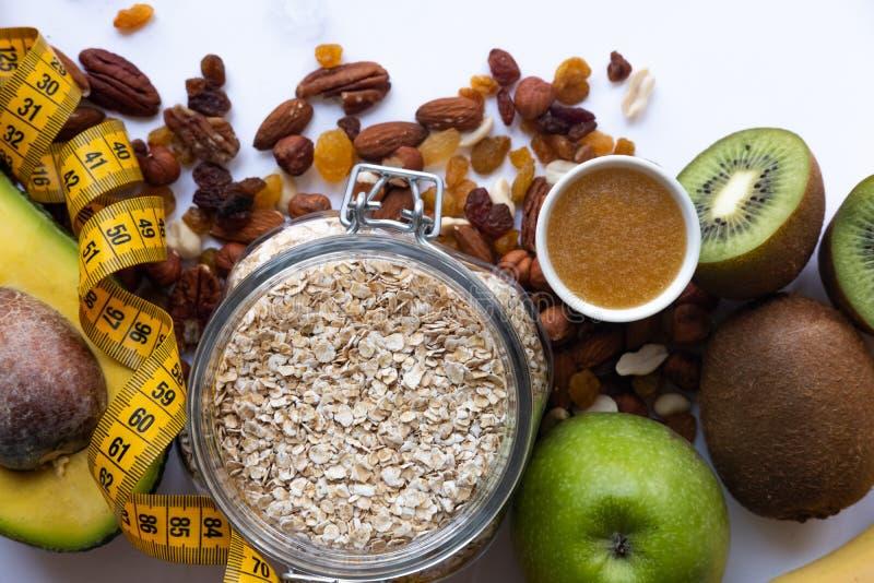 Sunda frukostingrediens Hemlagad granola i den öppna exponeringsglaskruset, honung, muttrar, frukter, gul band-gränd på vit bakgr royaltyfri foto