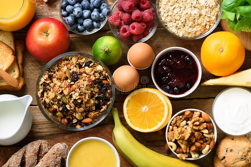 Sunda frukostingredienser, matram Granola ägget, muttrar, frukter, bär, rostat bröd, mjölkar, yoghurten, orange fruktsaft royaltyfria bilder