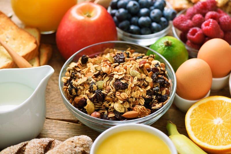 Sunda frukostingredienser, matram Granola ägget, muttrar, frukter, bär, rostat bröd, mjölkar, yoghurten, orange fruktsaft arkivfoto