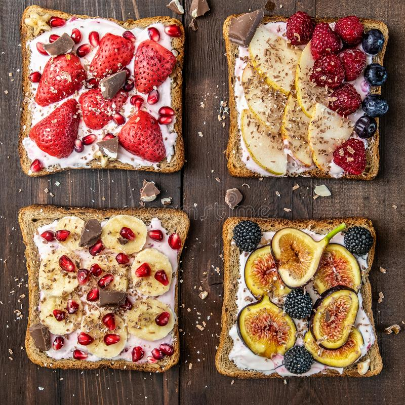 Sunda frukostskivor av wholegrain rostade bröd med gräddost, olik frukt, frö och muttrar Top beskådar arkivbilder