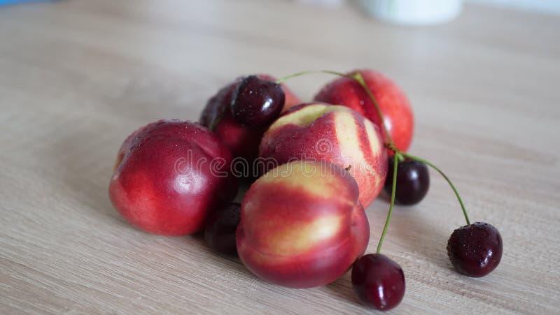 Sunda körsbär och persikor på trätabellen royaltyfri bild