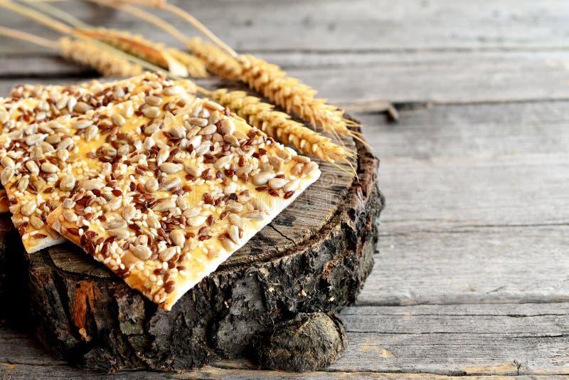 Sunda kakor med solrosfrö, linfrö och sesamfrö och spikelets av vete på gammal träbakgrund royaltyfri bild