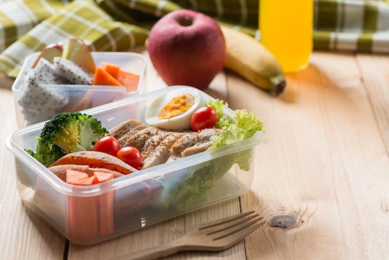 Sunda lunchaskar i plast- packe, grillat fegt bröst med sötpotatis-, ägg- och grönsaksallad, frukt, orange fruktsaft arkivbilder