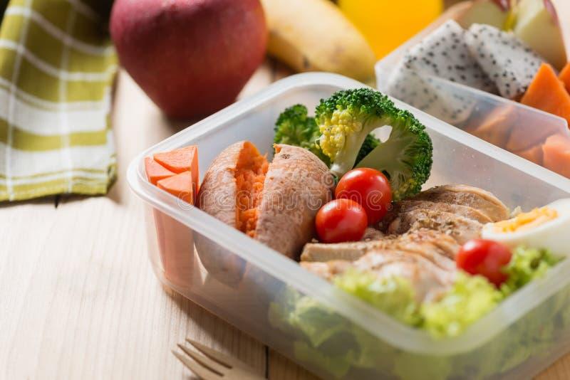 Sunda lunchaskar i plast- packe, grillat fegt bröst med sötpotatis-, ägg- och grönsaksallad, frukt, orange fruktsaft arkivfoton