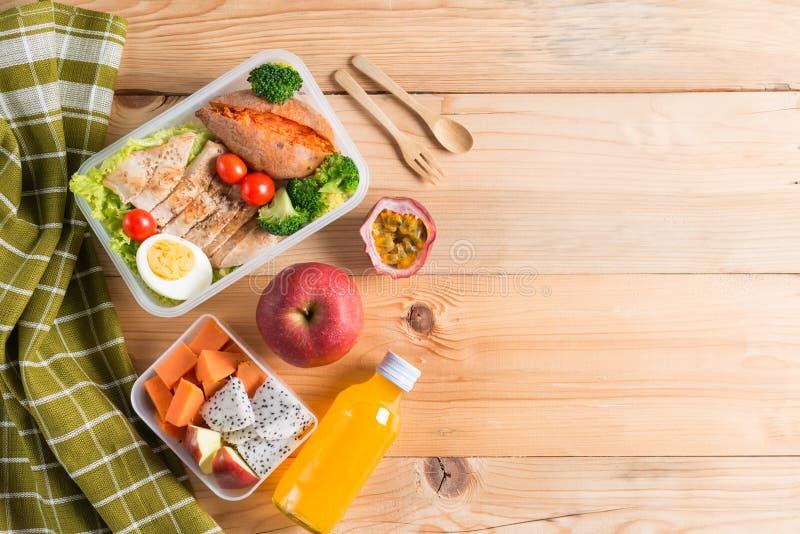 Sunda lunchaskar i plast- packe, grillat fegt bröst med sötpotatis-, ägg- och grönsaksallad, frukt, orange fruktsaft arkivbild