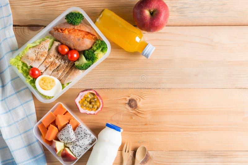 Sunda lunchaskar i plast- packe, grillat fegt bröst med sötpotatis-, ägg- och grönsaksallad, frukt, orange fruktsaft, royaltyfri fotografi