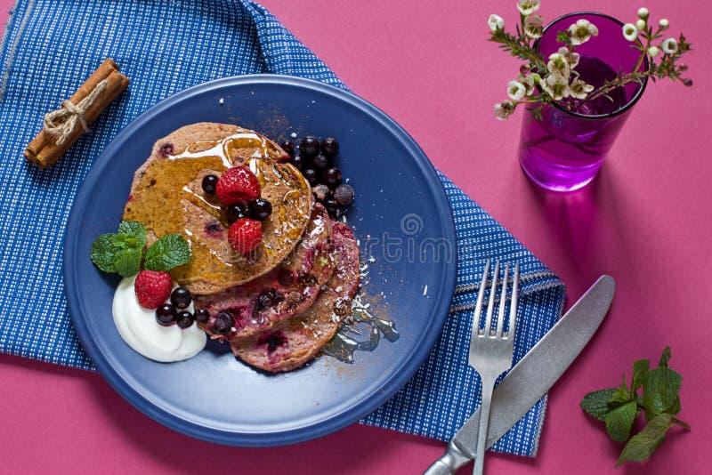 Sunda magra hemlagade pannkakor göras med banansmoothien, havre, kakaopulver och bär på plattan Fri morgon för socker royaltyfri bild