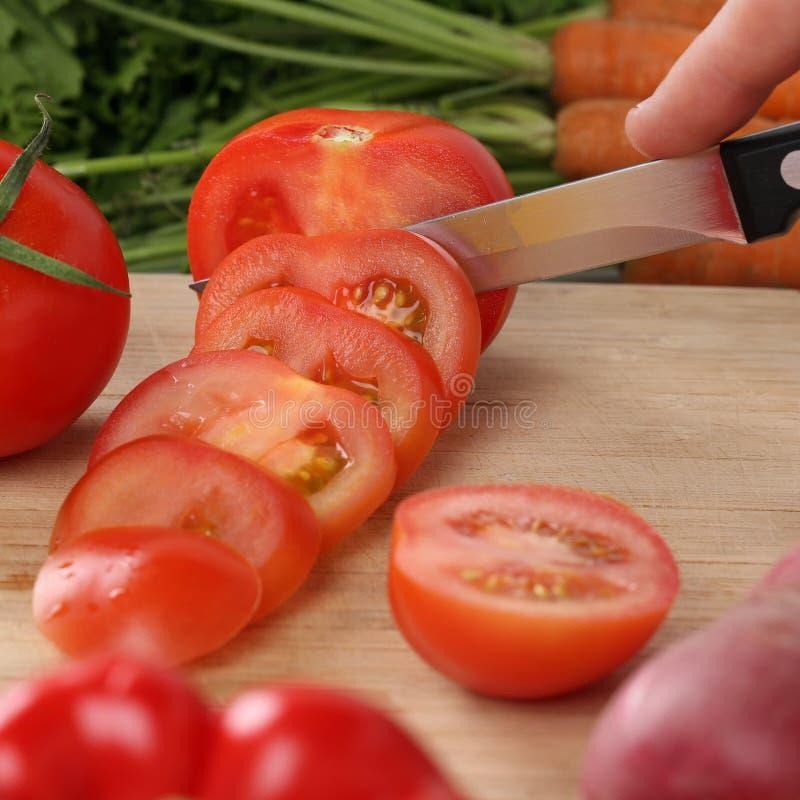 Sunda mattomatgrönsaker som skivar på ett kök, stiger ombord royaltyfri foto