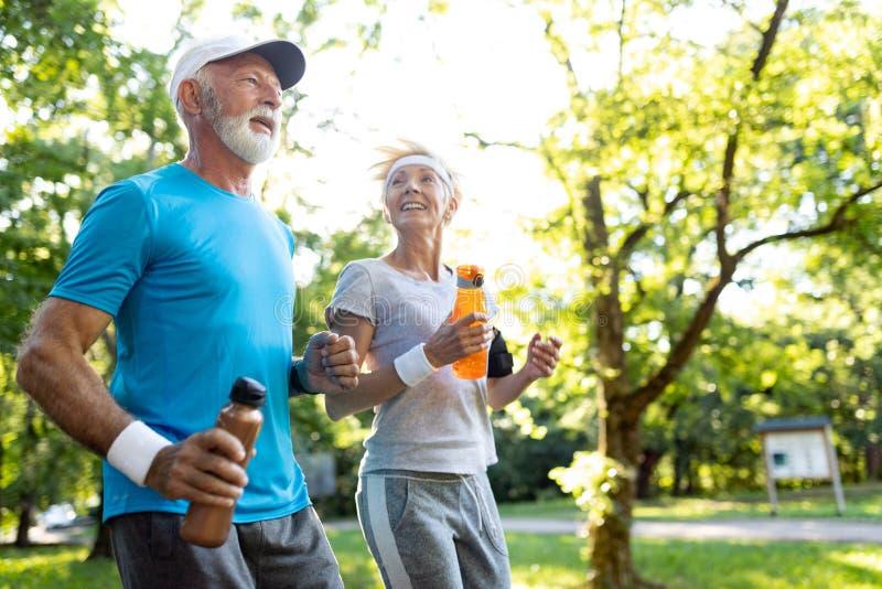 Sunda mogna par som joggar i, parkerar på ottan med soluppgång royaltyfria bilder