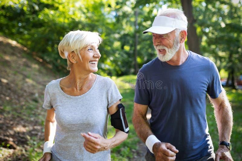 Sunda mogna par som joggar i, parkerar på ottan med soluppgång royaltyfri bild
