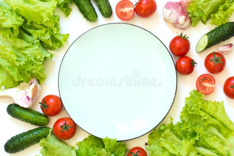 Sunda nya grönsaker för sallad runt om plattan Rå grön letuce, gräsplaner, tomat över den vita countertopen Top beskådar kopiera  royaltyfri fotografi