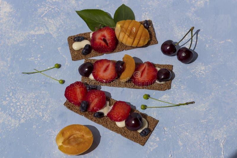 Sunda och smakliga rostade bröd med ostmassaost, frukter och bär på en blå bakgrund arkivbilder