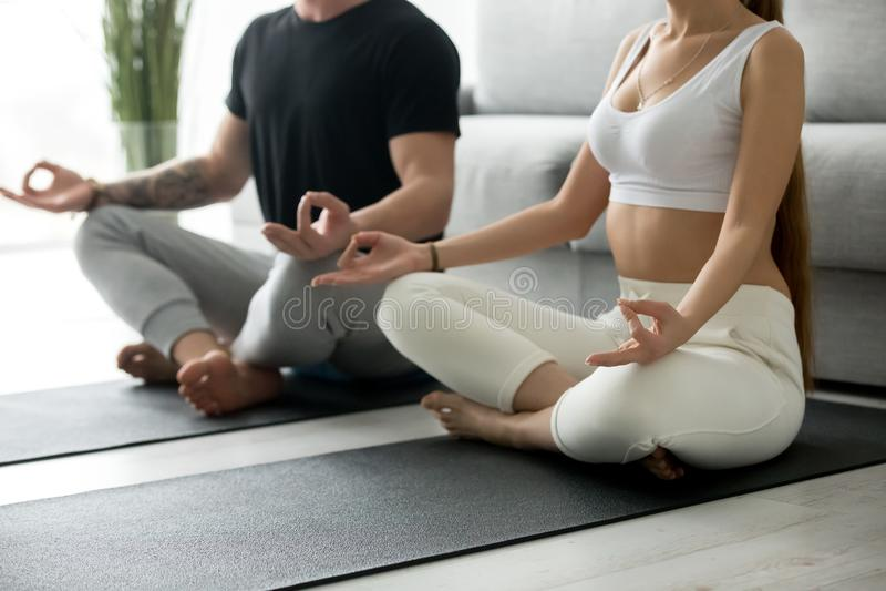 Sunda par som tillsammans gör praktiserande meditation för hem- yoga, c royaltyfri foto