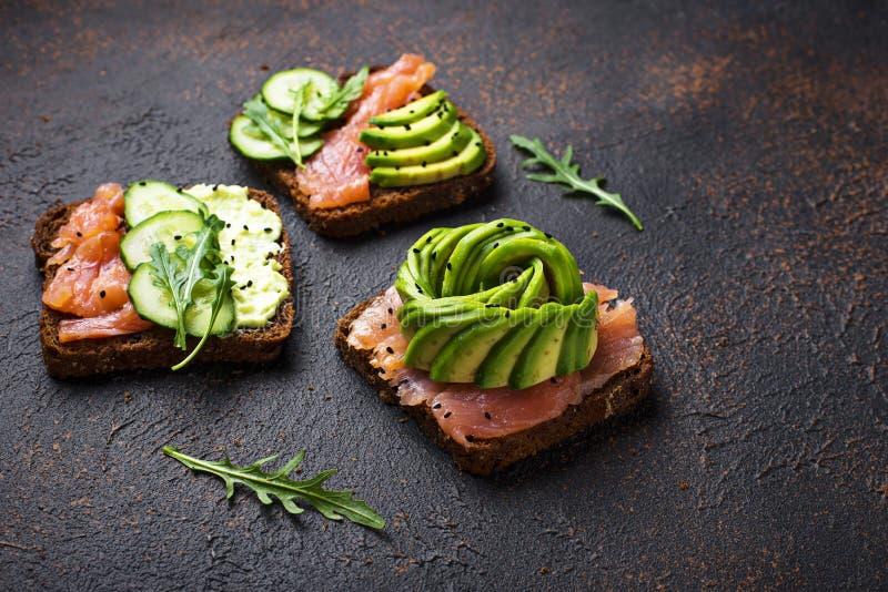 Sunda rostade bröd med lax- och avokadorosen royaltyfria foton