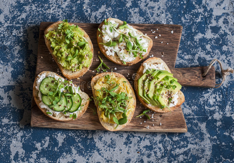 Sunda smörgåsar med avokadot, hummus, ricotta, gurkan, solrosgroddar, microgräsplaner och linfrö På ett träklipp bo arkivbild