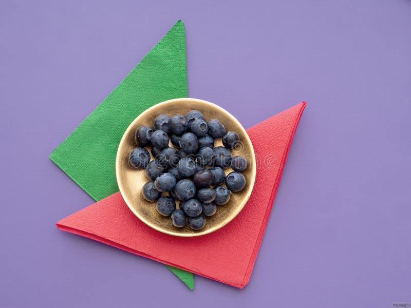 Sunda superfoodblåbär på färgglad bakgrund med pappers- servetter, servetter och den guld- plattan arkivbilder
