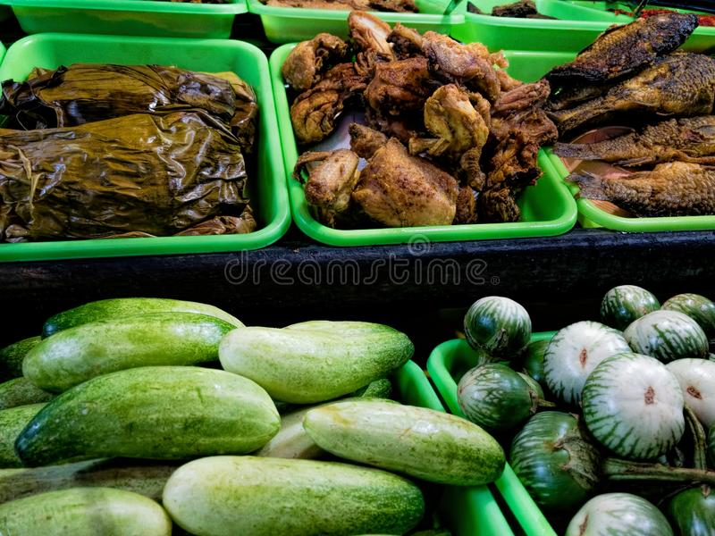 Sunda traditional street food night market seller. With its salad like cucumber and round egg plant. Meal are fried Chicken and fish stock photography