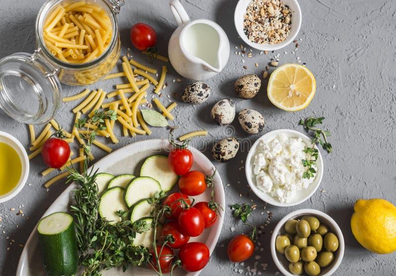 Sunda vegetariska matingredienser - pasta, zucchini, tomater, örter, kryddor, strikt vegetarianost, olivolja, citron, oliv På en  royaltyfria bilder