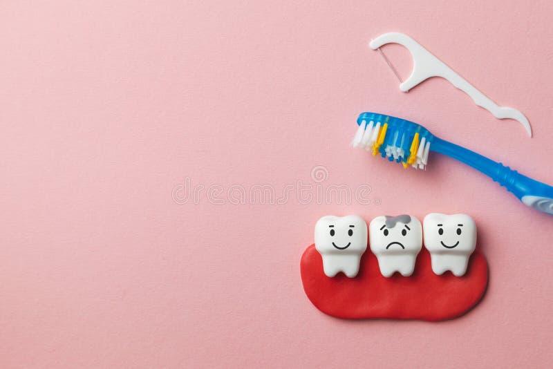 Sunda vita tänder ler, och tanden med karies är ledsen på rosa bakgrund och tandborsten och tandtråd Kopiera utrymme för royaltyfri fotografi