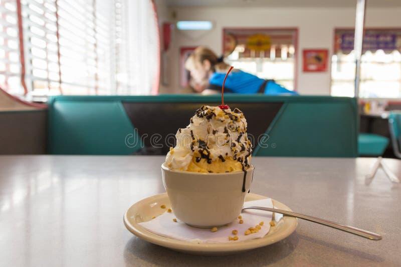 Sundae w małej filiżance ustawiającej na gościa restauracji stole z kelnerką pracuje w miękkim ostrości tle fotografia stock
