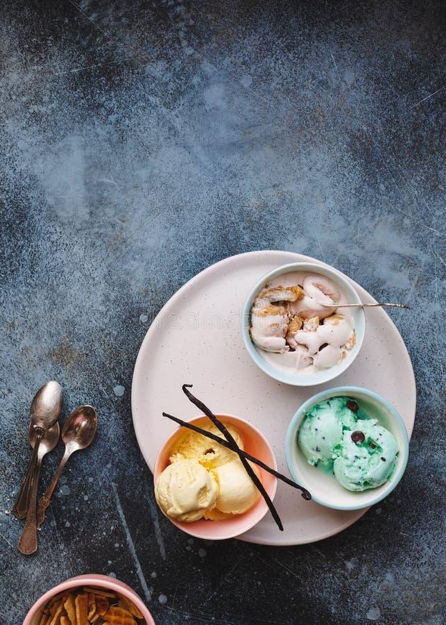 Sundaes deliciosas do gelado em umas bacias coloridas pasteis diferentes fotografia de stock