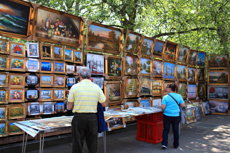 Sunday art exhibition, Bayswater Road, London. London, UK - Apr 24, 2011: Tourist looking for paintings at the regular Sunday art exhibition, in Bayswater Road royalty free stock image