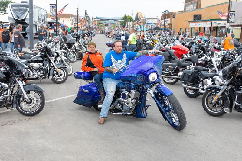 A couple rolling out down Main Street in Sturgis, South Dakota, on a stunning custom blue motorcycle. SUNDAY, AUGUST 5, 2018, STURGIS, SD: A man and woman royalty free stock image