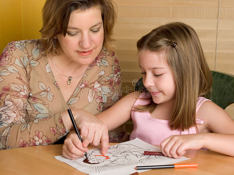 Sunday Lessons. A woman teaching a little girl about Jesus, as the girl colors a picture of him (could be Sunday School image royalty free stock photography