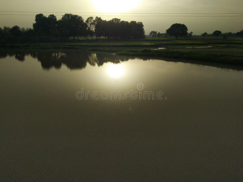 Sunday sunset sunshine rays water pond lake trees. Sunday sunset sunshine rays water pond lake stock images