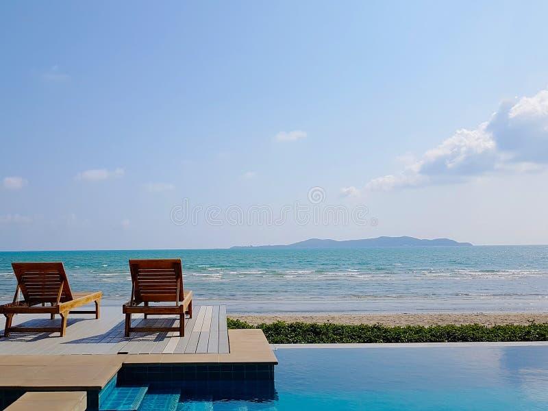 Sundeck eller bänk på havssikt med den privata simbassängen för semester på sommartid och härlig klar himmel i bakgrunden, arkivbild