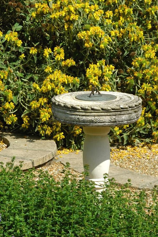 Sundial. Masonry sundial in a summer garden setting royalty free stock photos