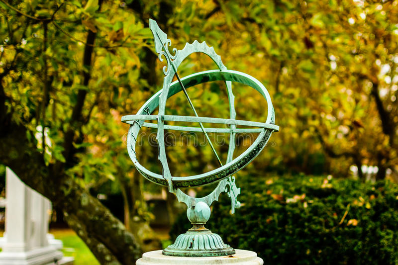 Sundial. Mounted turquoise sundial in landscaped park setting royalty free stock images