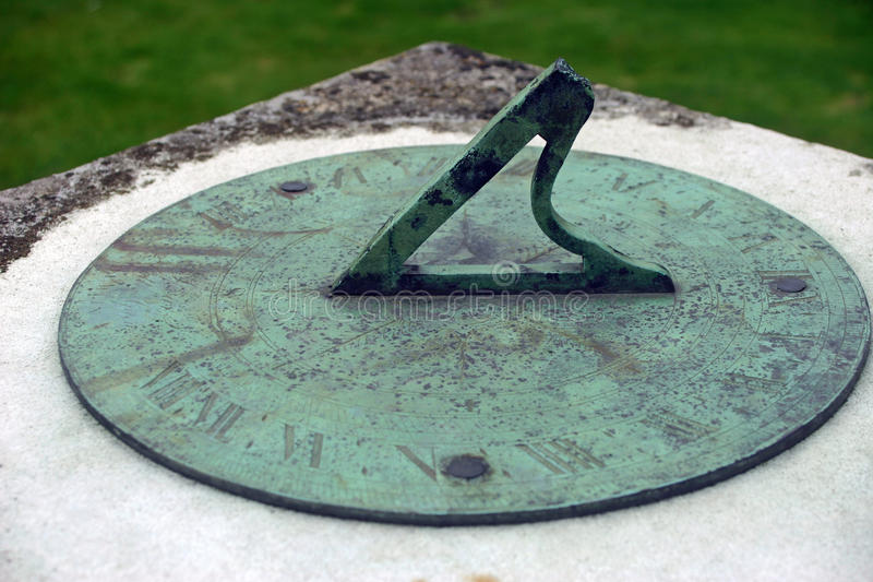 Sundial. On plinth. Probably made from brass as it has tarnished green. Not enough sun to show the time. Backgound is lawn grass stock photo