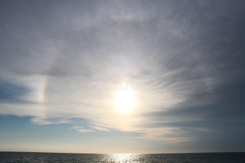 Sundog rätt för solnedgång över havet arkivfoton