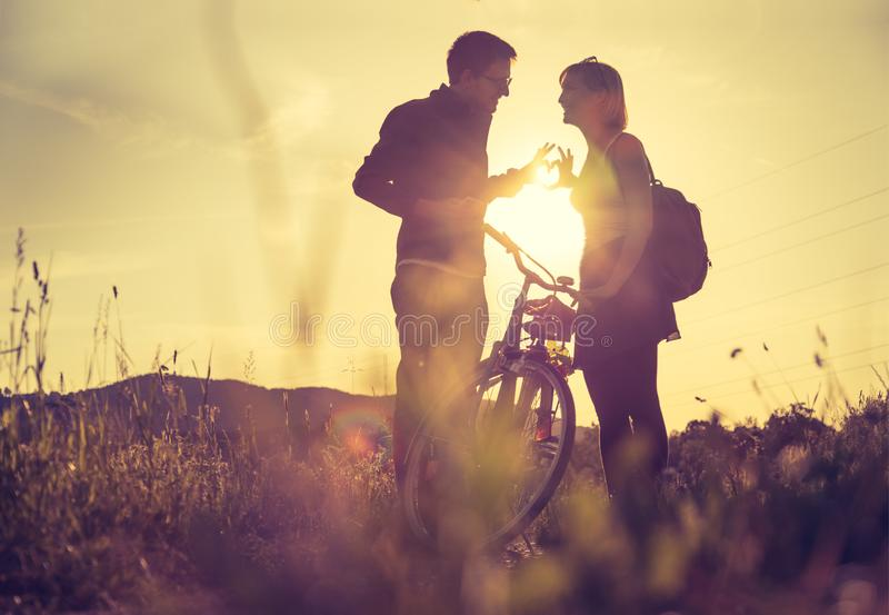 Sundown scenery with young couple: Boy and girl are doing a gesture royalty free stock photos