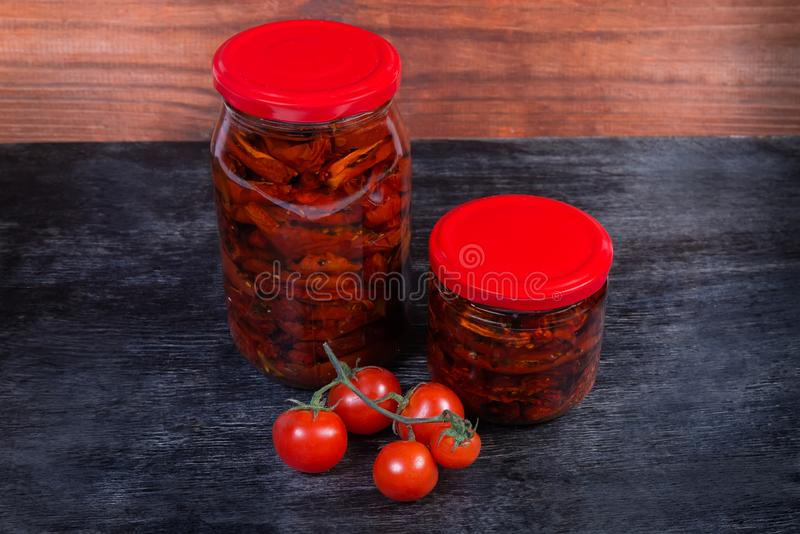 Sundried tomatoes in olive oil in glass jars, fresh tomatoes stock photo