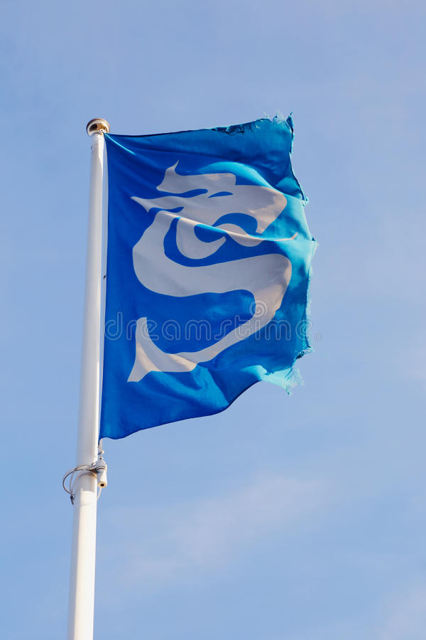 Sundsvall municipality flag. Sundsvall, Sweden - July 24, 2016: The flag with the symbol of the Sundsvall municipality raised on on flagpole royalty free stock images