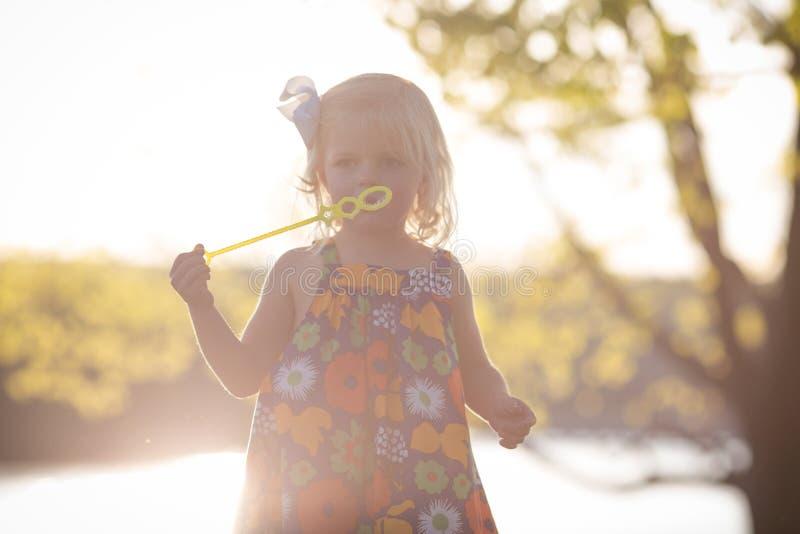 Sunflare het Kaukasische meisje spelen bij zonsondergang met bellen royalty-vrije stock foto's