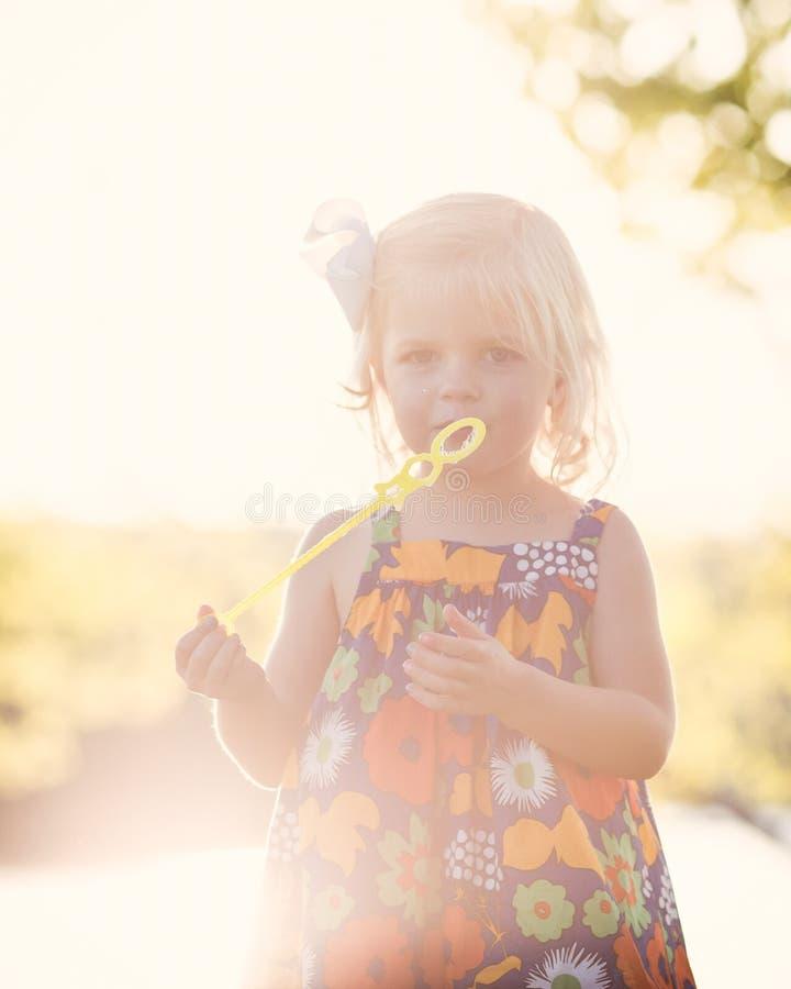 Sunflare het Kaukasische meisje spelen bij zonsondergang met bellen stock afbeelding