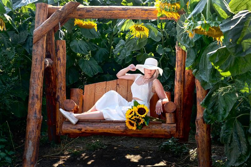 Carefree woman with sunflowers on swings looking calm and relaxed. stock image