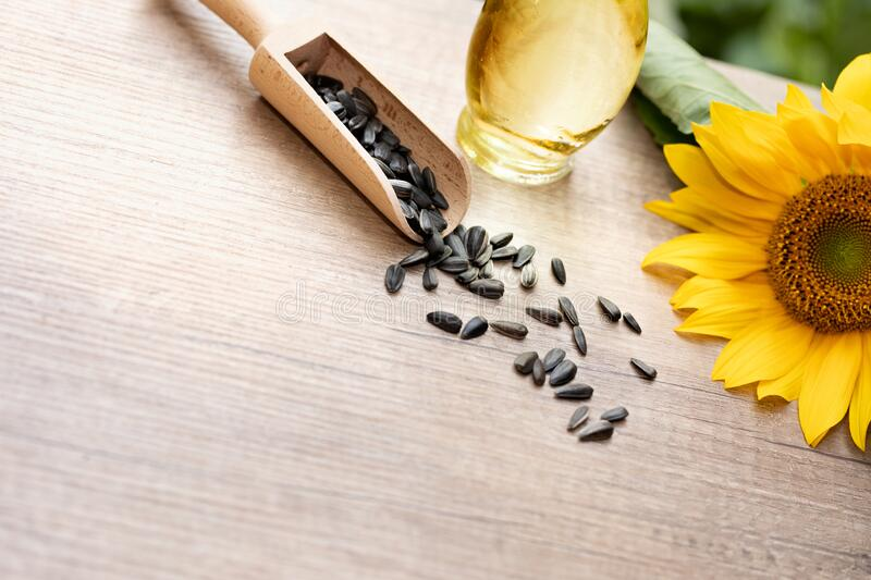 Sunflower oil in bottle glass with seed. And copy space on wooden table royalty free stock images