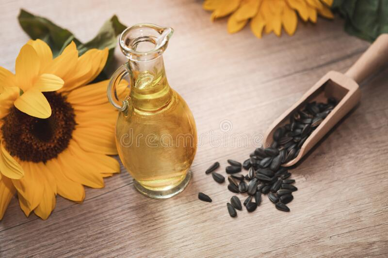 Sunflower oil. Organic sunflower oil in a small glass jar with sunflower seeds and fresh flowers. Outdoors stock images