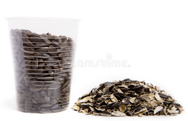 Sunflower seeds. In plastic glass and husk royalty free stock photo