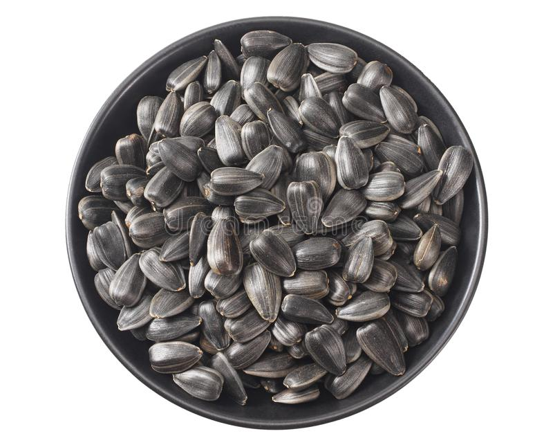 Sunflower seeds in a black plate isolated on white background. top view stock photo
