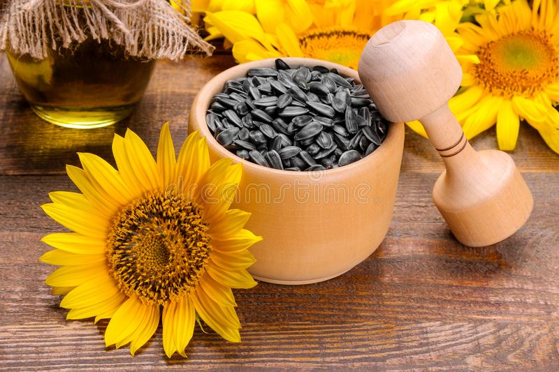 Sunflower seeds in a wooden crush and yellow sunflowers on a brown wooden background. Sunflower seeds in a wooden crush and bright yellow sunflowers on a brown stock photos