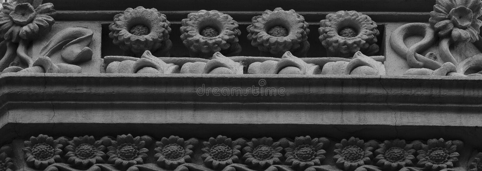 Sunflowers conquering the balcony. Shot in black and white detail on the sculpture on the facade of this historic building representing some characters / animals stock images